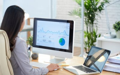 asian-businesswoman-sitting-desk-office-studying-graphs-large-computer-screen_1098-20500